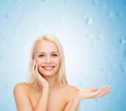 Smiling woman holding imaginary lotion jar Royalty Free Stock Photos