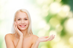 Smiling woman holding imaginary lotion jar Stock Images