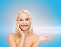 Smiling woman holding imaginary lotion jar Royalty Free Stock Image