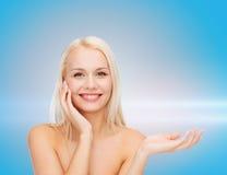 Smiling woman holding imaginary lotion jar Royalty Free Stock Image
