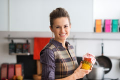 Smiling woman holding jar of vegetables in kitchen Royalty Free Stock Images