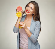 Smiling woman holding juice glass with half orange and grapefrui Stock Images