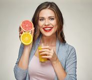 Smiling woman holding juice glass with half orange and grapefrui Royalty Free Stock Photos