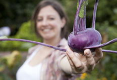 A smiling woman holding a Kohl Rabi Stock Image