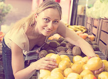 Smiling woman holding lemons in hands in fruit store Royalty Free Stock Photo