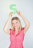 Smiling woman holding the letter S Stock Photo