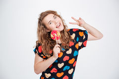 Smiling woman holding lollipop and showing peace sign Royalty Free Stock Photos