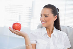 Smiling woman holding and looking at red apple Royalty Free Stock Photography