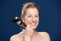 Smiling woman holding makeup brushes Stock Photography