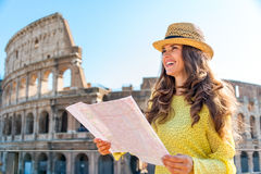 Smiling woman holding map of Rome at Colosseum in Rome Royalty Free Stock Images