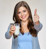 Smiling woman holding milk glass shows thumb up. Isolated portrait Stock Photos