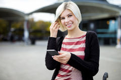 Smiling Woman Holding Mobile Phone Outside Railroad Station Royalty Free Stock Photos