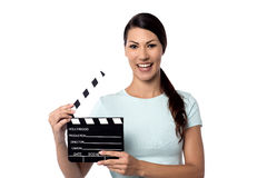Smiling woman holding a movie slate in hand Stock Photography