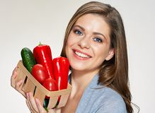 Smiling woman holding near face small basket. Smiling woman holding near face small basket with red vegetables. isolated face close up portrait Royalty Free Stock Images