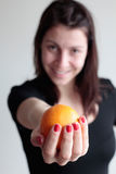 Smiling woman holding orange. Smiling woman in defocus holds an orange in focus Stock Images