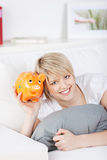 Smiling woman holding an orange piggy bank Stock Photography