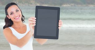 Smiling woman holding out tablet against blurry beach royalty free stock photos