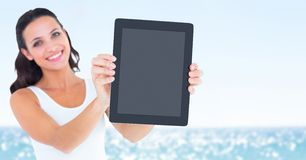 Smiling woman holding out tablet against blurry water on sunny day royalty free stock photos