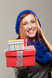 Smiling woman holding out two gift boxes. Beautiful smiling woman in winter fashion holding out two colourful gift boxes for Christmas, anniversary, Valentines Stock Images