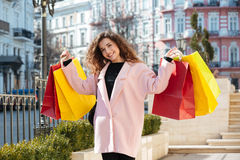 Smiling woman holding packages. Smiling woman in coat holding packages while standing on the street and looking at the camera royalty free stock images