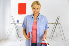 Smiling woman holding paint can with red paint swatch on wall in background Royalty Free Stock Photo