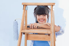 Smiling woman holding paint roller leaning on ladder Royalty Free Stock Images