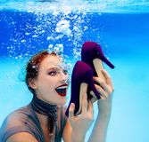 Smiling woman holding a pair of shoes underwater in the swimming pool. Smiling woman holding a pair of high heels shoes underwater in the swimming pool royalty free stock image