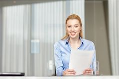 Smiling woman holding papers in office Stock Image