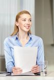 Smiling woman holding papers in office Royalty Free Stock Photography
