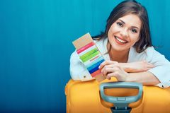 Smiling woman holding passport with ticket. Big yellow suitcase for travel Stock Photos