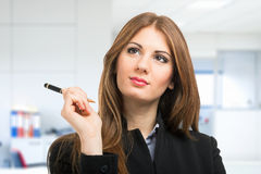 Smiling woman holding a pen Stock Photography
