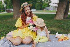 Smiling woman holding peonies play and have fun with little child baby girl smell flowers on green grass in park. Mother royalty free stock photography