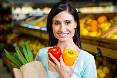 Smiling woman holding pepper and grocery bag Royalty Free Stock Image