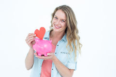 Smiling woman holding piggy bank and red heart Royalty Free Stock Photography