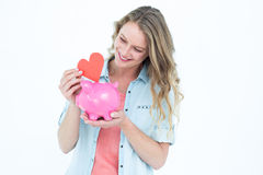 Smiling woman holding piggy bank and red heart Royalty Free Stock Photo