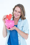 Smiling woman holding piggy bank and red heart Royalty Free Stock Photos