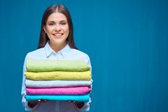 Smiling woman holding pile of towels. Stock Photos