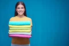 Smiling woman holding pile of towels. Royalty Free Stock Photography