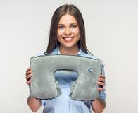 Smiling woman holding pillow for travel. Isolated white background Stock Photo