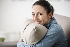 Smiling woman holding a pillow royalty free stock photography