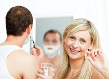 Smiling woman holding pills and man shaving Royalty Free Stock Photography