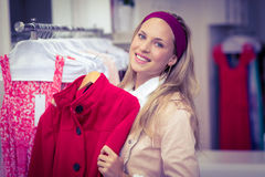 Smiling woman holding red coat Stock Images