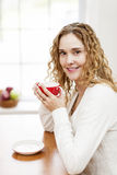 Smiling woman holding red coffee cup Stock Photos