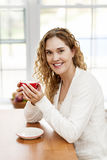 Smiling woman holding red coffee cup Stock Image