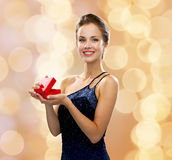 Smiling woman holding red gift box. Holidays, presents, luxury and happiness concept - smiling woman in dress holding red gift box over beige lights background Royalty Free Stock Photo