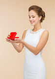 Smiling woman holding red gift box. Holidays, presents, wedding and happiness concept - smiling woman in white dress holding red gift box over beige background Royalty Free Stock Photo