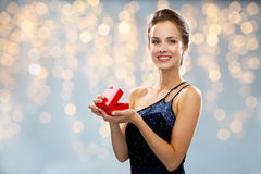 Smiling woman holding red gift box over lights Royalty Free Stock Images