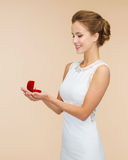 Smiling woman holding red gift box with ring Royalty Free Stock Images