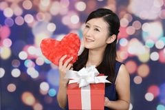 Smiling woman with a gift. Smiling woman holding red heart love symbol Royalty Free Stock Image
