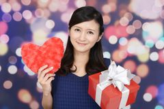 Smiling woman with a gift. Smiling woman holding red heart love symbol Stock Images